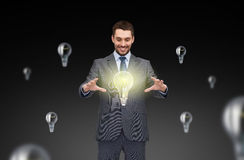 Businessman working with light bulb icons Stock Photos