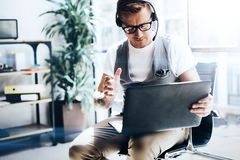 Businessman working at modern office on his digital tablet holding in hands.Handsome young man wearing audio headset and royalty free stock photos