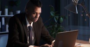 Businessman working at night in dark office. African american businessman working on laptop at night in dark office stock video
