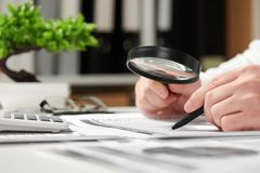 Businessman working in office and calculating finance. Using magnifying glass. Business financial accounting concept royalty free stock image