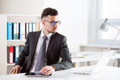 Businessman working in an office. Businessman working with computer in an office Stock Photos