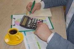 Man working on office desk with Calculator, a pen and document. Man, counting money and making calculations. Businessman working on office desk with Calculator stock photo