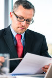 Businessman is working at office desk Stock Photos