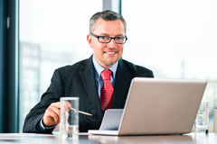 Businessman is working at office desk Stock Image