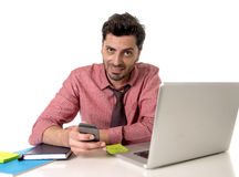 Businessman working at office desk texting with mobile phone in front of computer laptop smiling  happy Royalty Free Stock Image