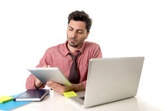 Businessman working at office desk using digital tablet pad sitting in front of computer laptop looking busy Royalty Free Stock Images