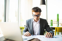 Businessman working at office with laptop, tablet and graph data documents on his desk. Royalty Free Stock Photography