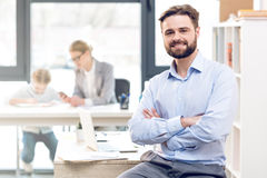 Businessman working in office, mother and daughter playing behind Stock Photos