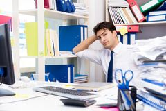 Businessman working in the office with piles of books and papers Stock Image