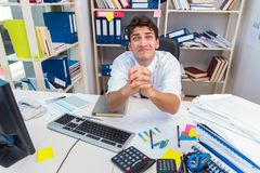Businessman working in the office with piles of books and papers Stock Images