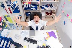Businessman working in the office with piles of books and papers Royalty Free Stock Photos