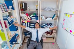 Businessman working in the office with piles of books and papers Stock Photo