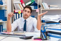 Businessman working in the office with piles of books and papers Royalty Free Stock Photo