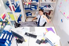 Businessman working in the office with piles of books and papers Royalty Free Stock Photography