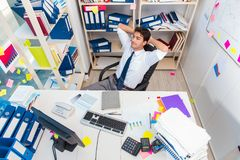 Businessman working in the office with piles of books and papers Royalty Free Stock Image