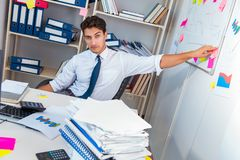 Businessman working in the office with piles of books and papers Royalty Free Stock Images