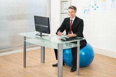 Businessman working in office sitting on pilates ball Stock Image