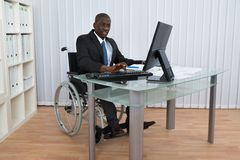 Businessman Working In Office Sitting On Wheelchair Royalty Free Stock Photography