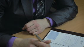 Businessman working in office. He wrote in the diary. stock video footage