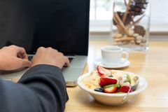 Businessman Working On Laptop And Having Bowl Of Yogurt With Fruit Salad And Coffee. Royalty Free Stock Image