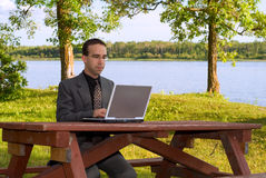 Businessman Working Outside. A young caucasian businessman working on a laptop computer outside in a park Stock Image