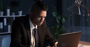 Businessman working overtime in office. African american businessman working overtime on office laptop stock footage