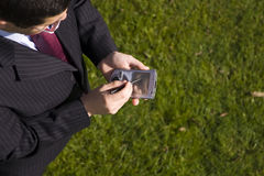 Businessman working with a palmtop. Above view of a businessman working with a palmtop (focus on the device Stock Photos