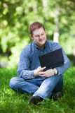 Businessman working in the park. Successful smiling businessman working with laptop in the city park Stock Photos