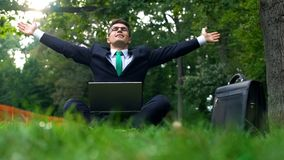 Businessman working in park taking rest and throwing hands up to sky, relaxation stock photos