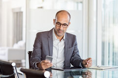 Businessman working on phone. Mature business man in formal clothing wearing spectacles using mobile phone. Serious businessman using smartphone and digital Royalty Free Stock Image