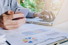 Businessman working with smart phone. And discussing the analysis charts or graphs on modern White office desk table .Close up business team analysis and Royalty Free Stock Images