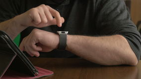 Businessman working on a smart watch and tablet pc in a coffee shop stock footage