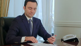 Businessman working with smartphone by desk in the office stock footage