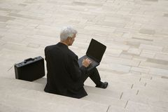Businessman working on steps. Stock Images