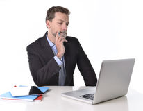 Businessman working in stress at office desk computer laptop reflexive and doubtful pensive and thoughtful Stock Photos