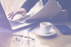 Businessman working at sunny office on laptop while sitting at the wooden table.Man holding paper documents in hands. Selective focus.Blurred background royalty free stock images