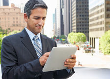 Businessman Working On Tablet Computer Outside Office. Outside Royalty Free Stock Photography