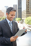 Businessman Working On Tablet Computer Outside Office. Smiling Royalty Free Stock Image