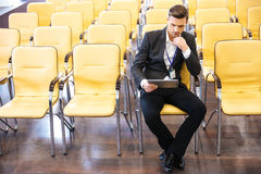Businessman working with tablet in conference hall Stock Photo