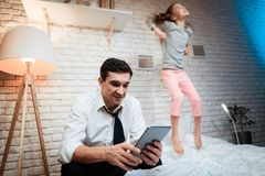 Businessman working on tablet. Little girl prevents her father from working. stock images