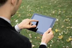 Businessman Working With Tablet PC. Businessman outdoors working with touch screen device Royalty Free Stock Photography
