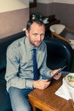 Businessman working on tablet pc during breakfast at home/hotel. Indoor photo Stock Image