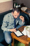 Businessman working on tablet pc during breakfast at home/hotel. Stock Image