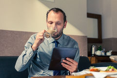 Businessman working on tablet pc during breakfast at home/hotel. Indoor photo Stock Photos