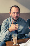 Businessman working on tablet pc during breakfast at home/hotel. Stock Images