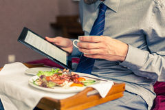 Businessman working on tablet pc during breakfast at home/hotel. Indoor photo Royalty Free Stock Images