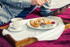 Businessman working on tablet pc during breakfast at home/hotel. Indoor photo Stock Photography