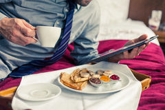 Businessman working on tablet pc during breakfast at home/hotel. Royalty Free Stock Photo