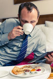Businessman working on tablet pc during breakfast at home/hotel. Royalty Free Stock Photography