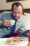 Businessman working on tablet pc during breakfast at home/hotel. Indoor photo Stock Photo